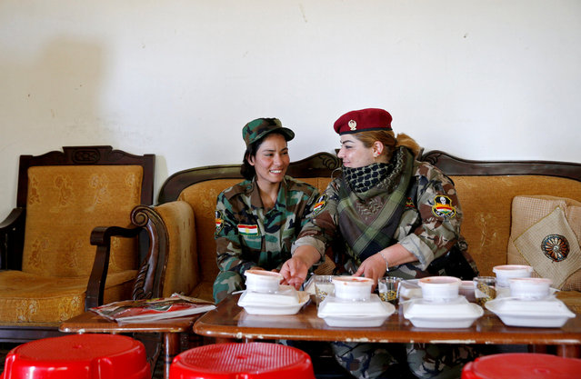 Iraqi Kurdish female fighter Haseba Nauzad (R), 24, and Yazidi female fighter Asema Dahir, 21, sit together to have their lunch at a site near the frontline of the fight against Islamic State militants in Nawaran near Mosul, Iraq, April 20, 2016. (Photo by Ahmed Jadallah/Reuters)