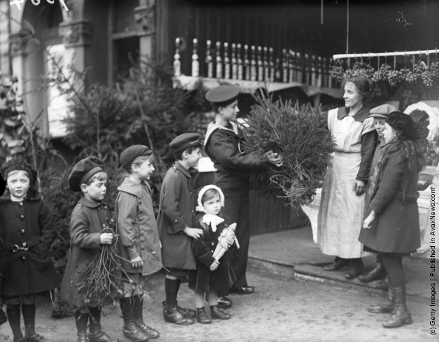 1918: A young sailor buys a Christmas tree at a greengrocer's and a young boy waits in a queue of children to buy some mistletoe