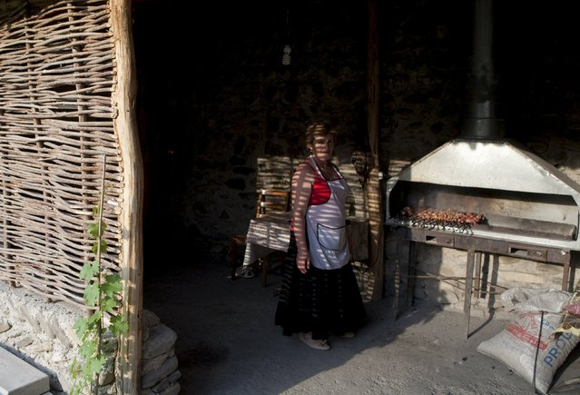A woman fries meat on a wood-fired grill at a cafe in Leningori (or Akhalgori), in the breakaway region of South Ossetia, Georgia, July 6, 2015. (Photo by Kazbek Basaev/Reuters)