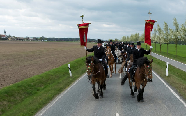 Sorbian men dressed in black tailcoats ride decorated horses during an Easter rider procession near Ralbitz, Germany April 16, 2017. (Photo by Matthias Rietschel/Reuters)