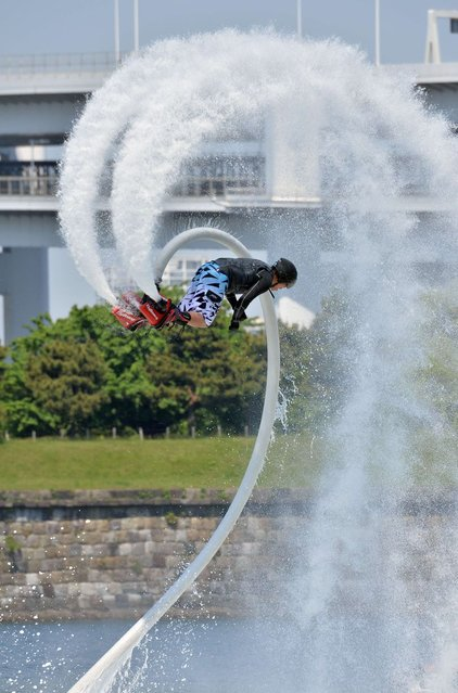 "A Japanese flyboard rider performs with a water-propelled flyboard which connects to a personal water craft with a hose during the Odaiba Beach Sports Festival in Tokyo on May 4, 2014. Holidaymakers enjoyed various beach and marine sports at an event for Japan's week-long ""Golden Week"" holiday. (Photo by Yoshikazu Tsuno/AFP Photo)"