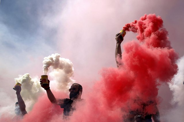Dinamo Bucharest ultra fans ignite smoke grenades in the club's colours white and red to pay tribute to Dinamo's Cameroonian midfielder Patrick Claude Ekeng as part of a farewell ceremony at the Dinamo Stadium in Bucharest, Romania, 13 May 2016. Ekeng collapsed during the Romanian Premier Soccer League playoff match between Dinamo Bucharest and Victoria at National Arena Stadium in Bucharest, Romania, 06 May 2016. (Photo by Robert Ghement/EPA)