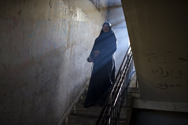 A woman walk downstairs in an abandoned building where refugees and migrants are living at a makeshift refugee camp at the northern Greek border point of Idomeni, Greece, on Saturday, May 14, 2016. Thousands of stranded refugees and migrants are camped at the makeshift refugee camp of the northern Greek border point of Idomeni. (Photo by Petros Giannakouris/AP Photo)