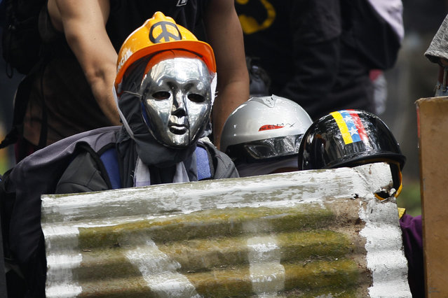 Masked demonstrators take cover during clashes with security forces at an opposition May Day march in Caracas, Venezuela, Monday, May 1, 2017. Venezuelans are taking to the streets in dueling anti- and pro-government May Day demonstrations as an intensifying protest movement enters its second month. (Photo by Ariana Cubillos/AP Photo)