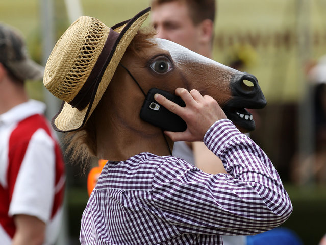 A fan in a horse mask talks on his cell phone before the 139th Preakness Stakes at Pimlico Race Course in Baltimore, MD, USA, on May 17, 2014. (Photo by Mitch Stringer/USA Today Sports)