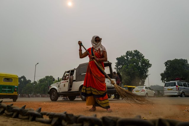 A woman sweeps a street near India Gate under heavy smog in New Delhi on October 29, 2019. Photo by Jewel Samad/AFP Photo)