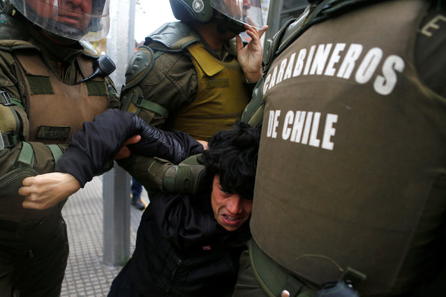 A demonstrator is detained during an unauthorized march called by secondary students to protest against government education reforms in Santiago, Chile, May 26, 2016. (Photo by Ivan Alvarado/Reuters)