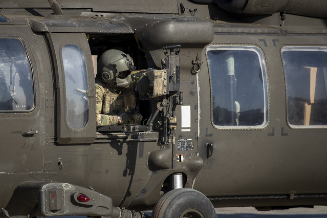 A helicopter gunner waits for takeoff at a US military base at an undisclosed location in Eastern Syria, Monday, November 11, 2019. The deployment of the mechanized force comes after US troops withdrew from northeastern Syria, making way for a Turkish offensive that began last month. (Photo by Darko Bandic/AP Photo)