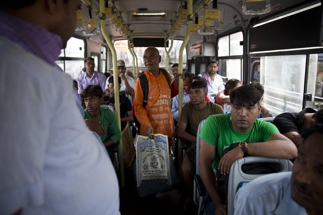"""In this June 27, 2015 photo, Omkarnath, center, who goes by the name """"Medicine Baba"""", takes a bus back home after collecting unused medicines from residential colonies in New Delhi, India. (Photo by Saurabh Das/AP Photo)"""