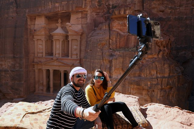 Tourists take selfie pictures in front of the treasury site in the ancient city of Petra, south of Amman, Jordan, November 21, 2019. (Photo by Muhammad Hamed/Reuters)
