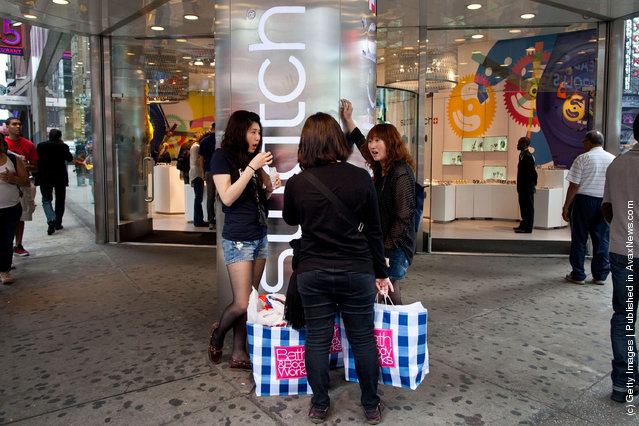 Women with shopping bags stand outside the Swatch store  in Times Square