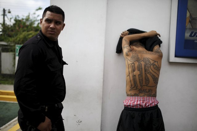 A policeman detains a suspected member of the MS-13 gang at a check point during the second day of a suspension of public transport services in Apopa, El Salvador July 28, 2015. (Photo by Jose Cabezas/Reuters)