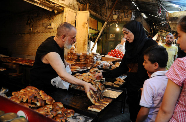 A vendor fills a bag with sweet bread on the first day of the holy fasting month of Ramadan in Tripoli, Lebanon June 6, 2016. (Photo by Omar Ibrahim/Reuters)