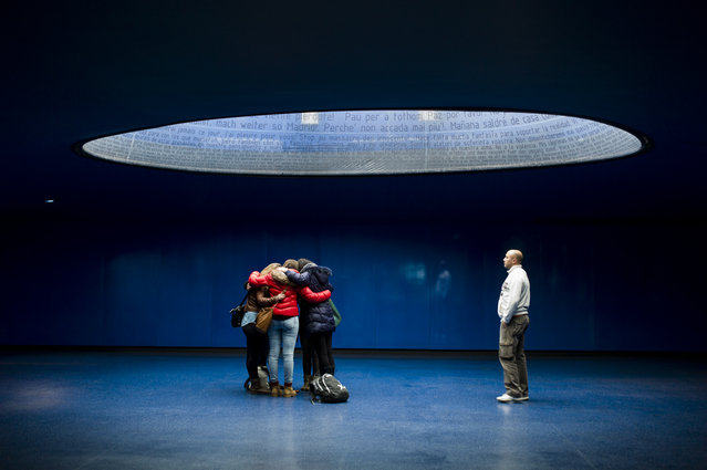 """Praying"". A group of people pray at Victims of March 11 Monument at Atocha Train Station in Madrid. Photo location: Spain. (Photo and caption by Tomas Calle/National Geographic Photo Contest)"