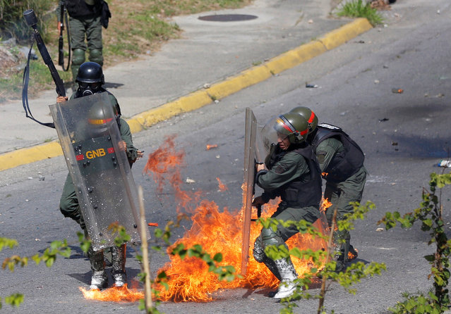 Members of the National Guard react after protesters threw a petrol bomb during a rally against Venezuela's President Nicolas Maduro's government in Caracas, Venezuela June 26, 2017. (Photo by Ivan Alvarado/Reuters)