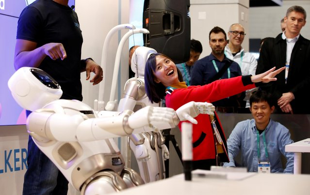 Tanli Yang, a journalist with China Global Television Network, performs yoga poses with Walker, an intelligent humanoid service robot, at the UB Tech booth during the 2020 CES in Las Vegas, Nevada, U.S. January 8, 2020. (Photo by Steve Marcus/Reuters)