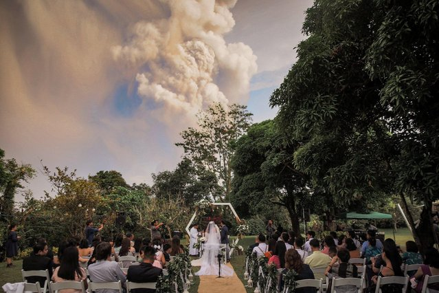 People attend a wedding ceremony as Taal Volcano sends out a column of ash in the background in Alfonso, Cavite, Philippines, January 12, 2020. (Photo by  Randolf Evan Photography/Social Media via Reuters)