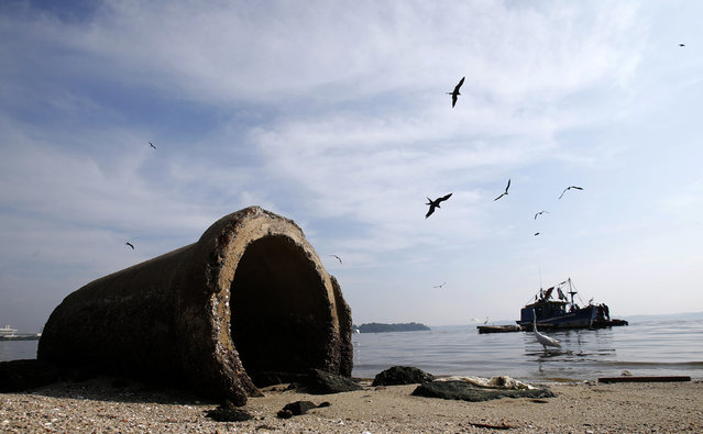 A pipe is seen near a fishing boat on Fundao beach in the Guanabara Bay in Rio de Janeiro March 13, 2014. (Photo by Sergio Moraes/Reuters)
