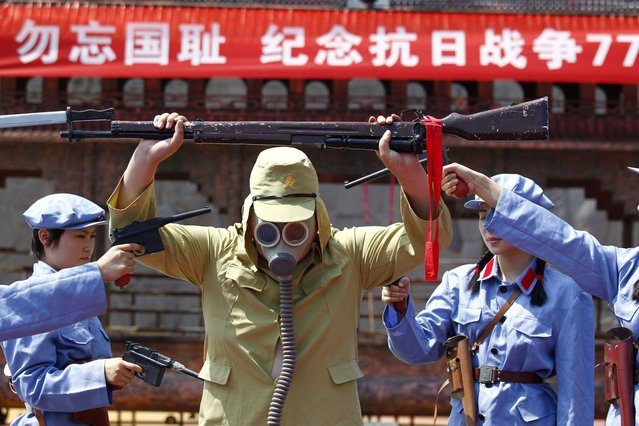 A group of Chinese women dressed in costumes depicting the famous Women's Detachment of the Red Army accept the surrender of a Japanese soldier (C) during a performance in Luanchuan, central China's Henan province on July 7, 2014, the 77th anniversary of the official start of war with Japan. (Photo by AFP Photo)