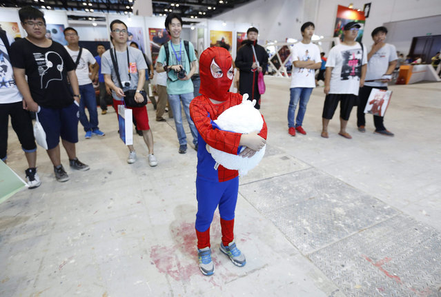 """A Chinese boy dressed up as """"Spider-Man"""" watches cartoons at the 2015 Animation and Comics Fair in Beijing, China, 24 July 2015. The fair is held from 24 to 26 July and is expected to attract more than 100,000 fans. (Photo by Wu Hong/EPA)"""