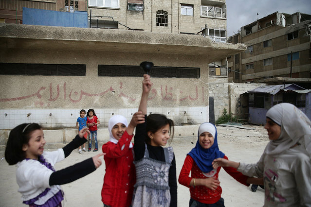 """Girls ring a bell inside a school yard in the town of Douma, eastern Ghouta in Damascus, Syria May 24, 2016. The writing on the wall reads in Arabic, """"Cleanliness is part of faith"""". (Photo by Bassam Khabieh/Reuters)"""