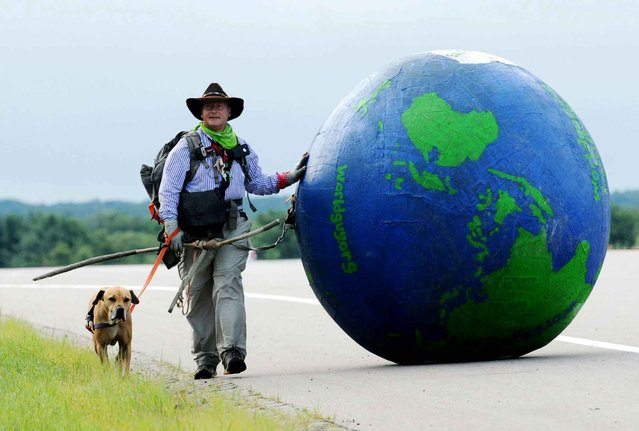 """Erik Bendl and his dog, Nice, walk along M-139, north of Berrien Springs, Mich., as they head toward St. Joseph, Mich., Wednesday, July 23, 2014. Bendl, 52, began his """"Walking the World For Diabetes Awareness"""" from his home in Louisville, Ky., on June 13 and has been averaging 10 miles each day. (Photo by Don Campbell/AP Photo/The Herald-Palladium)"""