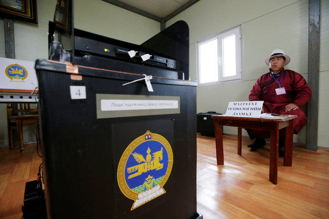 A polling office staff member sits next to the ballot box for the parliamentary elections at a polling station on the outskirt of Ulaanbaatar, Mongolia, June 29, 2016. (Photo by Jason Lee/Reuters)