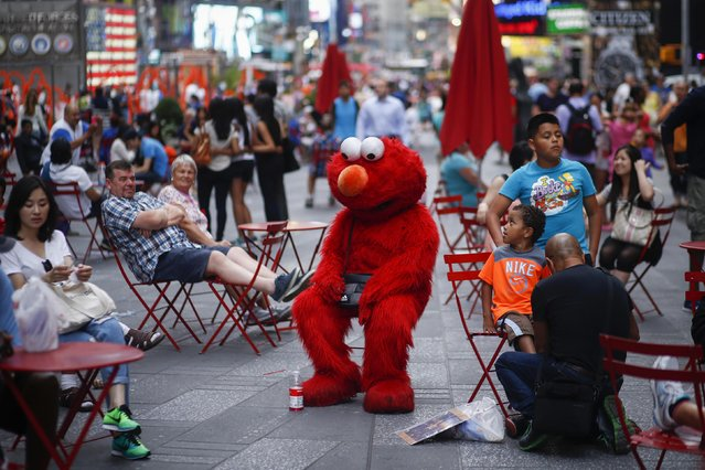 "Jorge, an immigrant from Mexico, dressed as the Sesame Street character Elmo rests in Times Square, New York July 29, 2014.  Elmo and Cookie Monster have long delighted young viewers on TV's ""Sesame Street"", but the recent antics of New York street performers dressed as the beloved characters have drawn the ire of city officials and now the show's producers. (Photo by Eduardo Munoz/Reuters)"