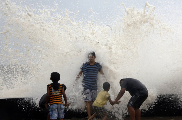 Waves during high tide hit the back of an Indian man at the Arabian Sea promenade in Mumbai, India, Wednesday, July 6, 2016. A new study released Friday in the journal Science Advances shows that man-made climate change is responsible for most of the change seen in ocean surface temperatures near the equator across Asia, which in turn affect regional rainfall patterns including the Indian monsoon. (Photo by Rajanish Kakade/AP Photo)