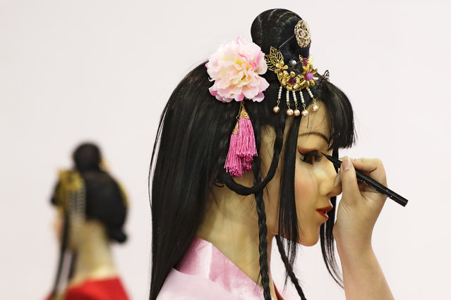 An exhibitor applies eyes make-up to a human-like robot on display at the World Robot Conference at the Yichuang International Conference and Exhibition Centre in Beijing, Wednesday, August 23, 2017. (Photo by Andy Wong/AP Photo)