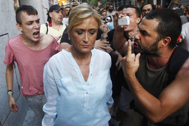 Demonstrators shout at the Spanish government's provincial representative, Maria Cifuentes, during a protest against austerity measures in Madrid on July 13, 2012. (Photo by Andres Kudacki/AP)