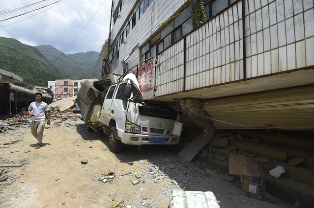 A villager walks past a damaged vehicle at an earthquake zone in Ludian county, Zhaotong, Yunnan province, August 5, 2014. An earthquake in China on the weekend triggered landslides that have blocked rivers and created rapidly growing bodies of water that could unleash more destruction on survivors of the disaster that killed 410 people, state media reported on Thursday. (Photo by Reuters/Stringer)