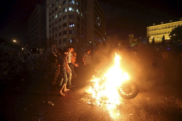 Protesters set a motorbike on fire during a protest against corruption and against the government's failure to resolve a crisis over rubbish disposal, near the government palace in Beirut, Lebanon August 23, 2015. Protests against the Lebanese government turned violent for a second day on Sunday, and Prime Minister Tammam Salam threatened to resign as public discontent brought thousands into the streets. (Photo by Hasan Shaaban/Reuters)