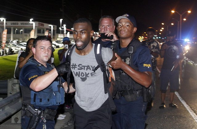 Police arrest activist DeRay McKesson during a protest along Airline Highway, a major road that passes in front of the Baton Rouge Police Department headquarters Saturday, July 9, 2016, in Baton Rouge, La. Protesters angry over the fatal shooting of Alton Sterling by two white Baton Rouge police officers rallied Saturday at the convenience store where he was shot, in front of the city's police department and at the state Capitol for another day of demonstrations. (Photo by Max Becherer/AP Photo)