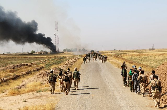 Kurdish Peshmerga fighters walk with their weapons as smoke rises from the site of clashes, south of Daquq, north of Baghdad August 26, 2015. (Photo by Reuters/Stringer)