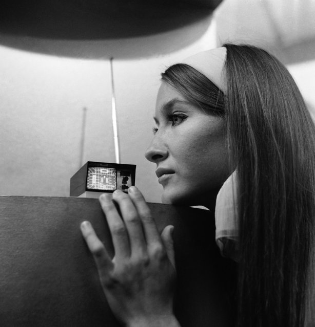 A pocket size television set that can go anywhere and claims to be the world's smallest TV, was presented at Earls Court, London on September 1, 1966. Miss Bari Lyn Chadwich of Cheshire looks at the Sinclair Micro vision set, designed by Clive Sinclair, a 26 year old Cambridge electronic engineer. Britain's midget TV set is powered by six ordinary penlight batteries. The rectangular face plate of the cathode tube has a diagonal measurement of two inches. The circuit uses 20 transistors, and covers channels 1 to 13 in Britain. (Photo by AP Photo)