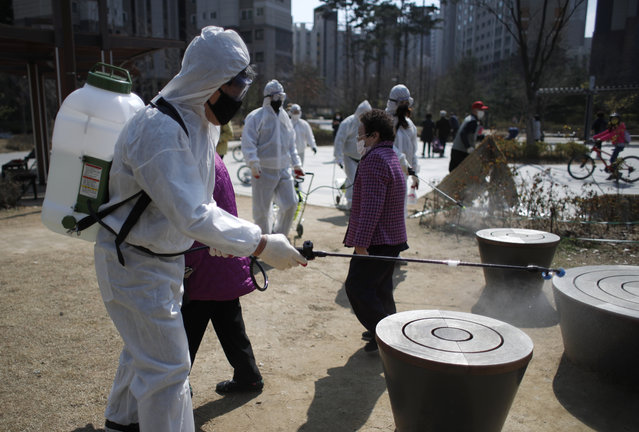 Members of a local residents group wear protective gear as they disinfect a local park as a precaution against the new coronavirus in Seoul, South Korea, Monday, March 23, 2020. (Photo by Lee Jin-man/AP Photo)