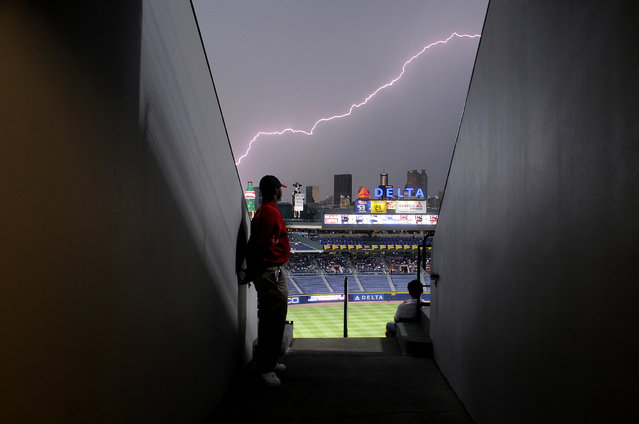 Usher Brent Mole stands along a wall as lightning strikes across the sky during a storm delay for the MLB National League baseball game between the Atlanta Braves and New York Mets at Turner Field in Atlanta, Georgia June 15, 2011. (Photo by Tami Chappell/Reuters)