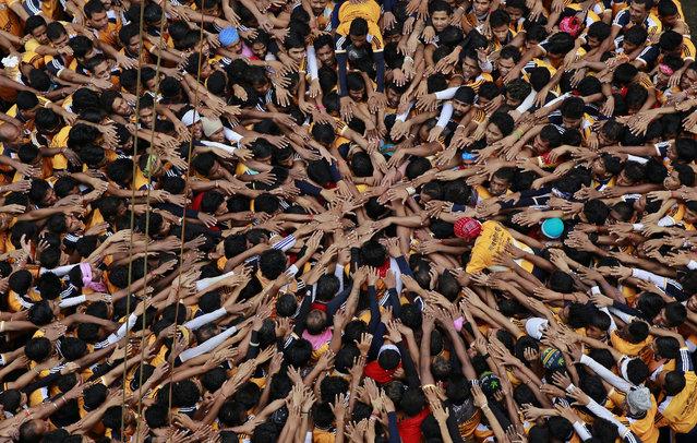 "Indian youth make a human pyramid to reach and break the ""Dahi Handi"", an earthen pot filled with yoghurt, as they celebrate Janamashtami in Mumbai, India, Monday, August 18, 2014. Janmashtami is the festival that marks the birth of Hindu god Krishna. (Photo by Rafiq Maqbool/AP Photo)"