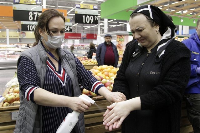 In this Monday, March 16, 2020, photo, a food mall staff, left, wearing a medical mask disinfects hands of a shopper in Chechen province capital Grozny, Russia. The Russian government says that it has decided to bar entry to all foreigners starting Wednesday. For most people, the new coronavirus causes only mild or moderate symptoms, such as fever and cough. For some, especially older adults and people with existing health problems, it can cause more severe illness, including pneumonia. (Photo by Musa Sadulayev/AP Photo)