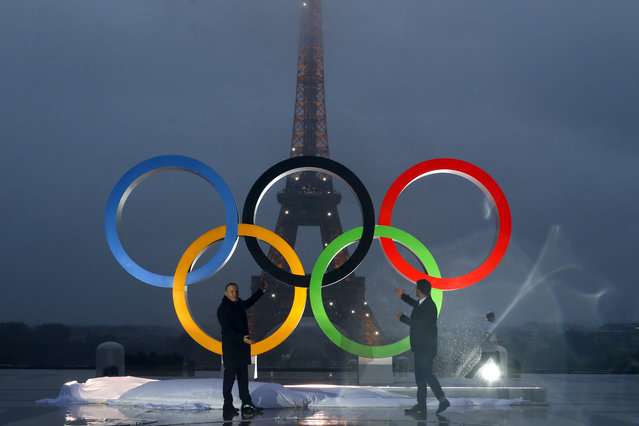 Paris officials unveil a display of the Olympic rings on Trocadero plaza that overlooks the Eiffel Tower, after the vote in Lima, Peru, awarding the 2024 Games to the French capital, in Paris, France, Wednesday, September 13, 2017. Paris will host the 2024 Summer Olympics and Los Angeles will stage the 2028 Games – a pre-determined conclusion that the International Olympic Committee has officially ratified in a history-making vote. (Photo by Francois Mori/AP Photo)
