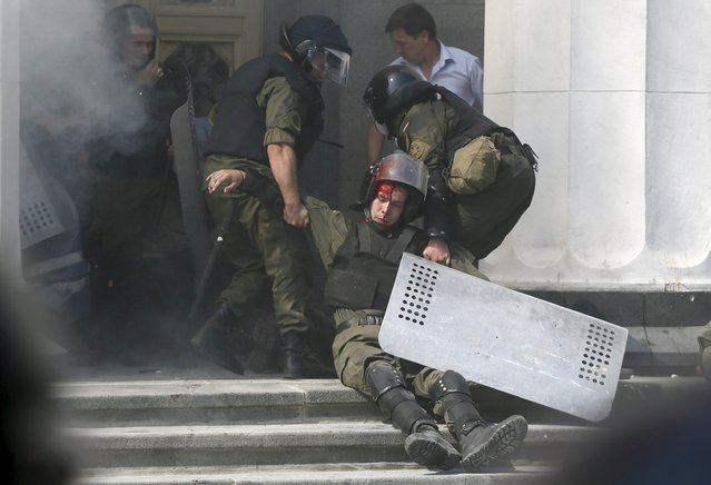 An injured national guard officer is carried away by comrades outside the parliament building in Kiev, Ukraine, August 31, 2015. Nearly 90 people were wounded and several of them were in a serious condition on Monday after several explosive devices were thrown from crowds in front of the Ukrainian parliament building in Kiev, the interior minister said in a Tweet. (Photo by Valentyn Ogirenko/Reuters)