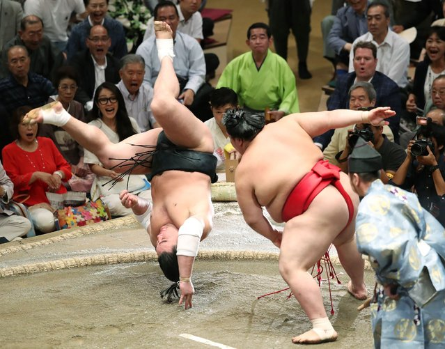"""Grand sumo champion, or """"yokozuna"""", Harumafuji (L) of Mongolia somersaults over to lose his bout against Onosho of Japan (R) on the fifth day of the 15-day Autumn Grand Sumo Tournament in Tokyo on September 14, 2017. (Photo by AFP Photo/JIJI Press)"""