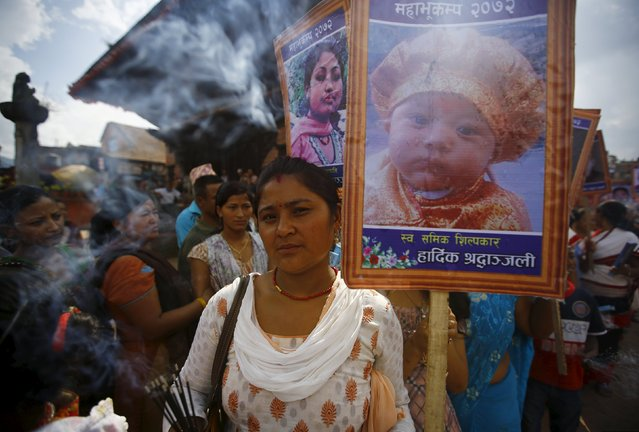 A woman carrying the portrait of her son who died during the April 25th earthquake takes part in a memorial rally in Bhaktapur September 2, 2015. (Photo by Navesh Chitrakar/Reuters)
