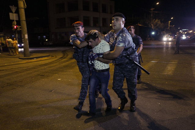 Police officers detain a supporter of the armed group who have been holding a police station in Yerevan, Armenia, early Wednesday, July 27, 2016. A spokesman for Armenia's police says two of the gunmen who have been holding a police station in the capital for more than a week have surrendered after an exchange of gunfire. Police spokesman Ashot Arahonyan says on Facebook that the gunfire began before dawn on Wednesday. (Photo by Vahan Stepanyan/PAN Photo via AP Photo)