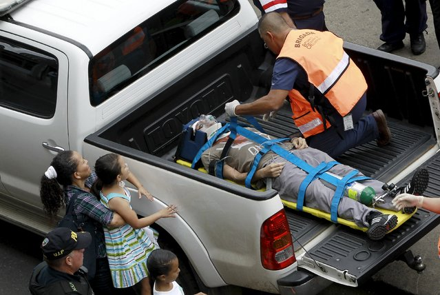"""A girl looks on as an office worker evacuates a man posing as an injured person during an earthquake evacuation drill in San Jose, Costa Rica, September 3, 2015. The disaster drill called """"Mi ciudad se prepara"""" (My City Prepares) was organized by the National Emergency Commission and nearly 60,000 people participated in over 90 buildings downtown that were evacuated, according to local media. (Photo by Juan Carlos Ulate/Reuters)"""