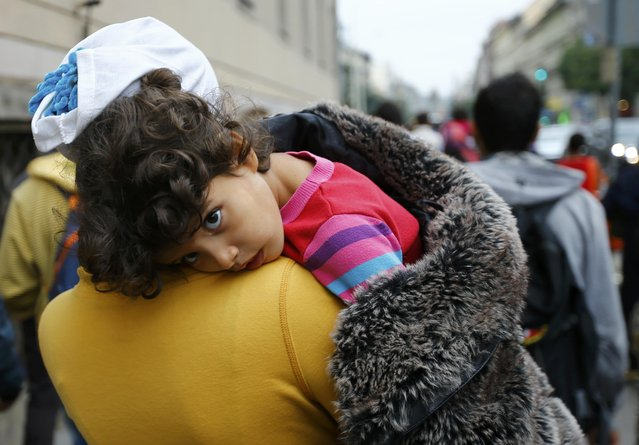 A migrant women holds her child as she walks down the street from Keleti train station in Budapest, Hungary, September 5, 2015. (Photo by Leonhard Foeger/Reuters)