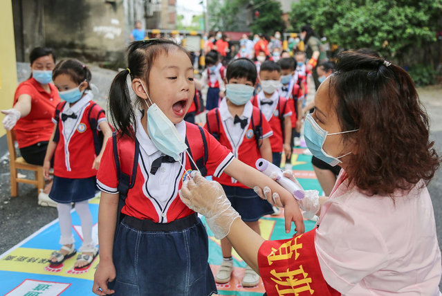 This photo taken on May 11, 2020 shows a staff member (R) checking the oral health of a child before she enters a kindergarten in Yongzhou in China's central Hunan province. China reported no new domestic coronavirus infections on May 12, after two consecutive days of double-digit increases fuelled fears of a second wave of infections. (Photo by AFP Photo/China Stringer Network)