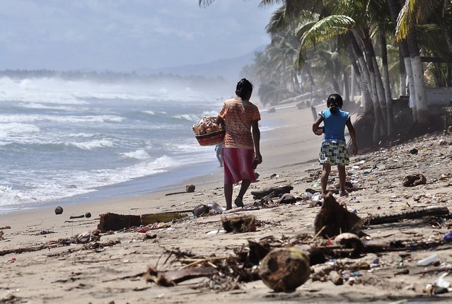 A woman and a girl walk along the beach covered in debris after Hurrican Odile hit the area, in Acapulco September 18, 2014. Thousands of tourists were stranded in the storm-battered Mexican Pacific resort of Los Cabos on Thursday, with water in short supply and looted stores sitting empty as a new hurricane threatened to buffet the popular tourist hub. (Photo by Claudio Vargas/Reuters)