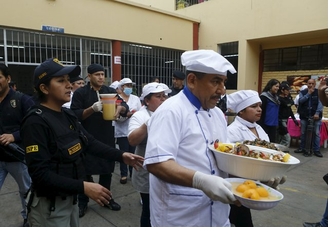 Inmates carry platters of food during a culinary competition at the Santa Monica female prison in Lima, September 10, 2015. (Photo by Mariana Bazo/Reuters)